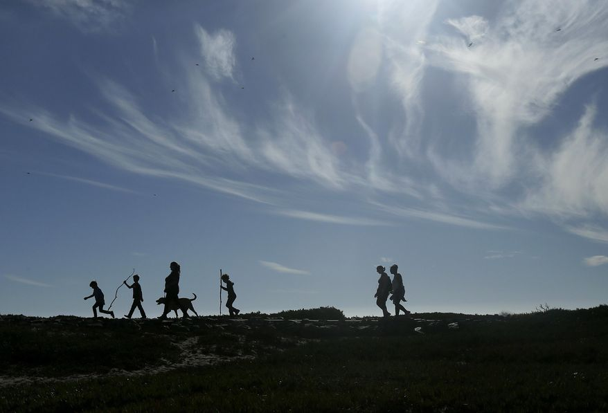 A group walks a dog on a path at Fort Funston in San Francisco, Friday, Sept. 23, 2016. The San Francisco Bay Area will see weekend sunshine and temperatures in the 70s and 80s. (AP Photo/Jeff Chiu)
