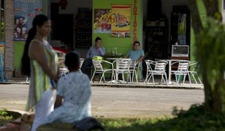 In this Wednesday, Sept. 21, 2016 photo, men drink beer at a store in the house where, in mid-2005, seven people were gunned down by rebels of the Revolutionary Armed Forces of Colombia, FARC, in Puerto Rico, southern Colombia. On May 24, 2005, members of an elite guerrilla platoon swept silently into town by boat, hopped on the back of a red pickup truck and drove a few blocks through a small police barrier to a house where a town hall meeting was taking place. They burst in with a machine gun spraying bullets and in less than 10 minutes killed seven people, including four city council members.  (AP Photo/Ricardo Mazalan)