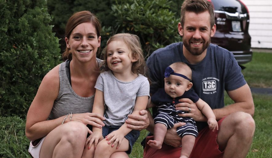 Ryan Smith, right, poses with his wife Sarah and children Ashton, 2, and Eden, 6 months, outside their family home, Tuesday, Sept. 20, 2016, in Cranston, Rhode Island. Both of the Smiths were able to take advantage of paid family leave with the birth of their daughter Eden. As both leading presidential candidates tout campaign proposals promising paid leave to take care of a newborn baby, three states, California, New Jersey and Rhode Island, already have programs available to parents. (AP Photo/Charles Krupa)