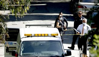 Investigators stand by the Los Angeles County coroners van after the body of a man was moved into it from a home in the Hollywood Hills section of Los Angeles, Friday, Sept. 23, 2016. Los Angeles police are searching for a suspect in the killing of a man at a home in the Hollywood Hills. The house is being rented by a former Canadian TV talk-show host George Stroumboulopoulos, who says the victim was a close friend who was staying there while he was in New York.  Police were called Friday to the neighborhood not far from the Hollywood Bowl.  (AP Photo/Nick Ut)
