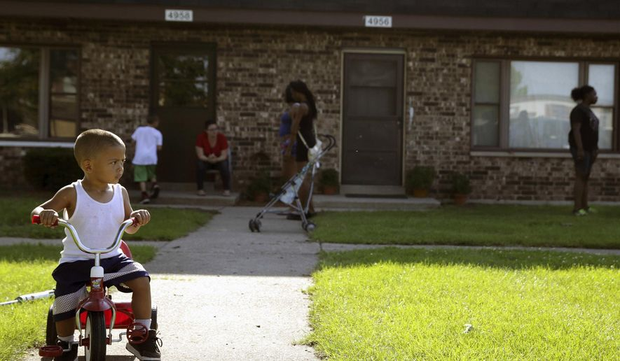 FILE - In this Aug. 3, 2016 file photo, Joseph Russell, 2, rides his tricycle outside his home at the West Calumet Housing Complex in East Chicago, Ind. The mayor of this industrial town ordered the evacuation of the 40-year-old public housing complex this summer because of severe lead contamination, forcing more than 1,000 people from their homes.(Jonathan Miano/The Times via AP, file)