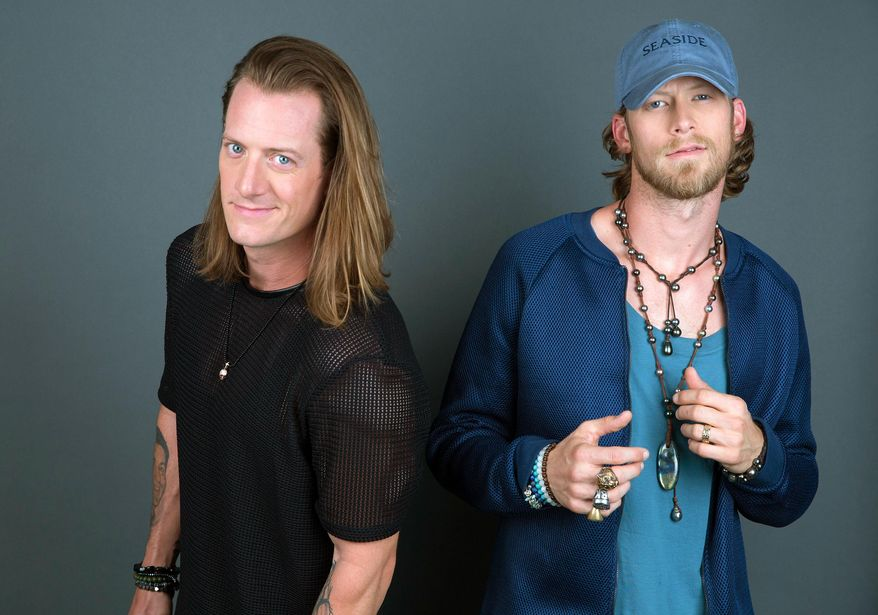 """In this Aug. 25, 2016 photo, Tyler Hubbard, left, and Brian Kelley of Florida Georgia Line pose for a portrait in New York to promote their latest album, """"Dig Your Roots. (Photo by Amy Sussman/Invision/AP, File)"""