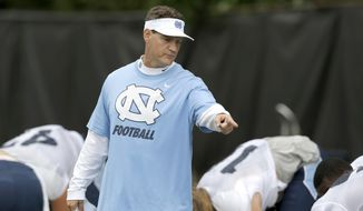"FILE - In this Aug. 10, 2015, file photo, North Carolina defensive coordinator Gene Chizik works with players during an NCAA college football practice in Chapel Hill, N.C. Chizik said the Tar Heels' defense played ""soft"" last week against James Madison and will have to play better against Pittsburgh ""or this game could get ugly."" (AP Photo/Gerry Broome, File)"