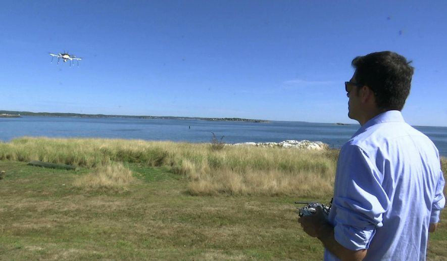 In this Thursday, Sept. 22, 2016 still image from video, aerospace engineer Felipe Bohorquez guides a test drone making a UPS delivery to Children's Island in Marblehead, Mass. UPS partnered with robot-maker CyPhy Works to fly the drone on a programmed route for three miles over the Atlantic Ocean to make the delivery. (AP Photo/Rodrique Ngowi)