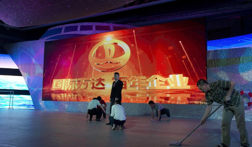 "FILE - In this June 19, 2013 file photo, Chinese workers prepare the stage ahead of a ceremony for Dalian Wanda Group at a hotel in Beijing, China. China's Dalian Wanda Group and Sony Pictures Entertainment Motion Picture Group have formed a partnership to cooperate on multiple big-budget movies, marking another step into the global film industry by the Chinese conglomerate. Chinese characters on screen reads ""International Wanda, Century Enterprise."" (AP Photo/Ng Han Guan, File)"