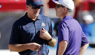 FILE - In this Nov. 15, 2014, file photo, Arizona head coach Rich Rodriguez, left, and Washington head coach Chris Petersen talk before an NCAA college football game in Tucson, Ariz. The Huskies get their first true test on Saturday against Arizona, after opening the season with three straight wins. (AP Photo/Rick Scuteri, File)