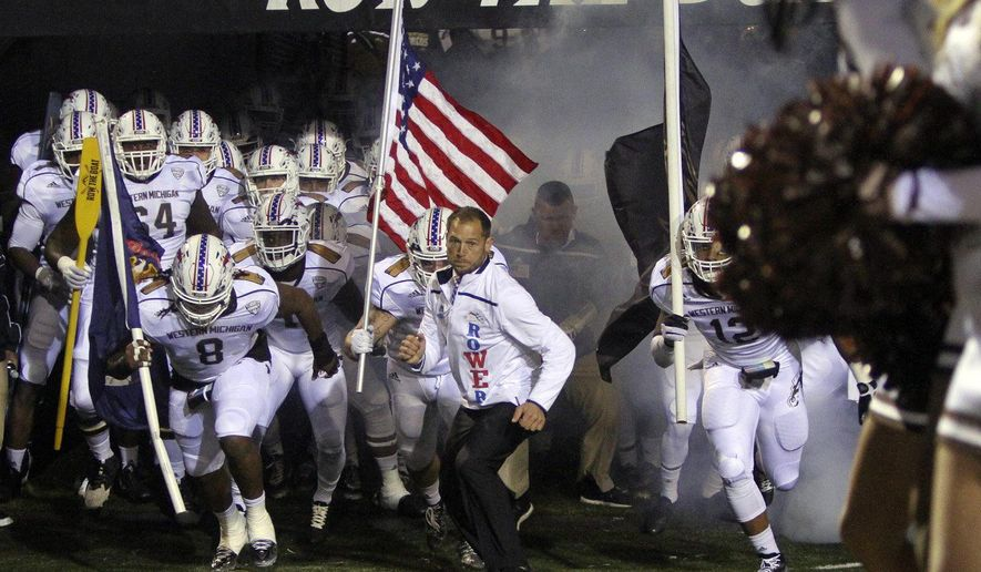 FILE - In this Nov. 11, 2015, file photo ,Western Michigan coach P.J. Fleck leads his team onto the field before an NCAA college football game against Bowling Green at Waldo Stadium in Kalamazoo, Mich.  The 35-year-old Fleck still talks with the same kind of energy he showed when he first took over the job before the 2013 season, and the program's catchphrase of Row the Boat resonates a little more when the team is winning.  (Daytona Niles /Kalamazoo Gazette-MLive Media Group via AP)