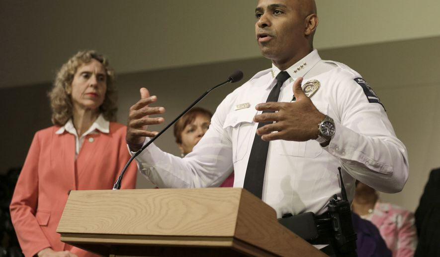 """FILE - In this Friday, Sept. 23, 2016 file photo, Charlotte-Mecklenburg Police chief Kerr Putney, right, gestures as Charlotte mayor Jennifer Roberts, left, watches in Charlotte, N.C., during a news conference concerning protests and the investigation into Tuesday's fatal police shooting of Keith Lamont Scott. Putney told reporters Friday that at least one body camera and one dashboard camera recorded footage of the shooting. He said """"it's a matter of when"""" the video will be released.  (AP Photo/Chuck Burton, File)"""