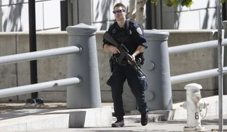 A San Francisco Police officer responds to the scene of a standoff of a possibly armed man in Civic Center Plaza in San Francisco, Saturday, Sept. 24, 2016.  (Michael Macor/San Francisco Chronicle via AP)