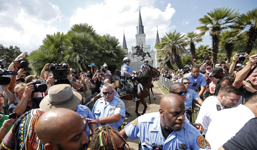 New Orleans police guard a statue of Andrew Jackson, in Jackson Square, during a protest organized by Take 'Em Down NOLA, who threatened to tear the statue down, in New Orleans, Saturday, Sept. 24, 2016. (AP Photo/Gerald Herbert) ** FILE **