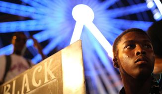 CORRECTS NAME TO TERENCE CRUTCHER A demonstrator holds a sign during a protest in Atlanta on Friday, Sept. 23, 2016 in response to the police shooting deaths of Terence Crutcher in Tulsa, Okla. and Keith Lamont Scott in Charlotte, N.C. (AP Photo/Branden Camp)