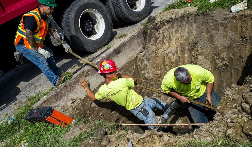 In a file photo from Aug. 31, 2016, crews break ground and work to remove and replace lead-tainted pipes from three homes during first day of the second phase under Mayor Karen Weaver's Fast Start program Wednesday, in Flint, Mich. (Jake May/The Flint Journal-MLive.com via AP)