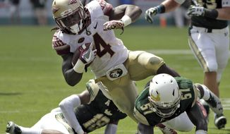 Florida State running back Dalvin Cook (4) is hit by South Florida linebacker Nigel Harris (57) on a run during the first quarter of an NCAA college football game Saturday, Sept. 24, 2016, in Tampa, Fla. (AP Photo/Chris O'Meara)