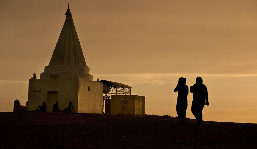 FILE - The sun sets as women visit a Yazidi shrine overlooking at Kankhe Camp for the internally displaced in Dahuk, northern Iraq, in this Wednesday, May 18, 2016 file photo. Lawyers in Europe investigating the Islamic State's elaborate operation to kidnap thousands of women as sex slaves say they have enough evidence to try IS leaders with crimes against humanity, but two years after the IS onslaught against the Yazidi people, the Obama administration has made little effort to pursue prosecution. Current and former U.S. State Department officials say that a push for a legal finding of genocide in late 2014 was quashed by the Defense Department. (AP Photo/Maya Alleruzzo, File)