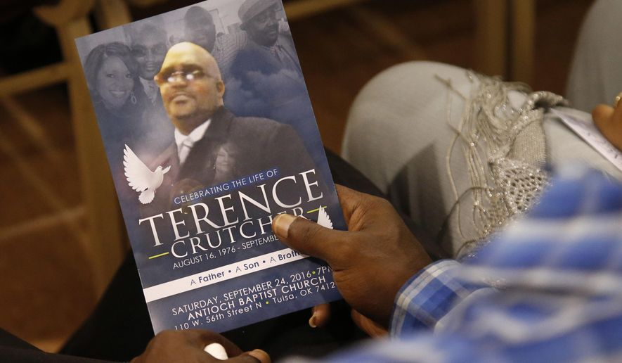 A man holds a copy of the program for the funeral of Terence Crutcher during services to honor him in Tulsa, Okla., Saturday, Sept. 24, 2016. Crutcher was fatally shot Sept. 16 by Officer Betty Jo Shelby. (AP Photo/Sue Ogrocki)