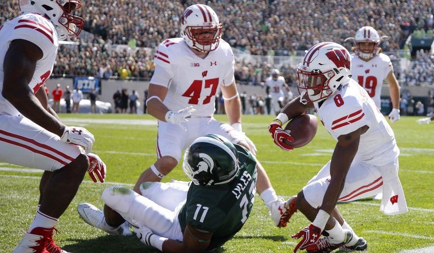 Wisconsin's Sojourn Shelton, right, Vince Biegel (47) and Leon Jacobs, left, celebrate Shelton's interception against Michigan State's Jamal Lyles (11) during the second quarter of an NCAA college football game, Saturday, Sept. 24, 2016, in East Lansing, Mich. (AP Photo/Al Goldis)