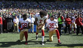 San Francisco 49ers Eli Harold (58), Colin Kaepernick (7) and Eric Reid (35) drop to a kneeling position at the beginning of the national anthem before an NFL football game against the Seattle Seahawks, Sunday, Sept. 25, 2016, in Seattle. (AP Photo/Ted S. Warren)