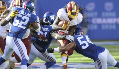 Washington Redskins' Matt Jones (31) rushes past New York Giants' Olivier Vernon (54) and Kelvin Sheppard (91) during the second half of an NFL football game Sunday, Sept. 25, 2016, in East Rutherford, N.J. (AP Photo/Bill Kostroun)