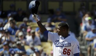 Los Angeles Dodgers' Yasiel Puig waves to Vin Scully, a Hall of Fame broadcaster who called his final regular season home game of his career covering the Dodgers, at a baseball game against the Colorado Rockies in Los Angeles, Sunday, Sept. 25, 2016. (AP Photo/Chris Carlson)