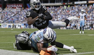 Tennessee Titans running back DeMarco Murray (29) scores a touchdown on a 5-yard run as he is hit at the goal line by Oakland Raiders defenders Bruce Irvin (51) and David Amerson (29) in the second half of an NFL football game Sunday, Sept. 25, 2016, in Nashville, Tenn. (AP Photo/Weston Kenney)