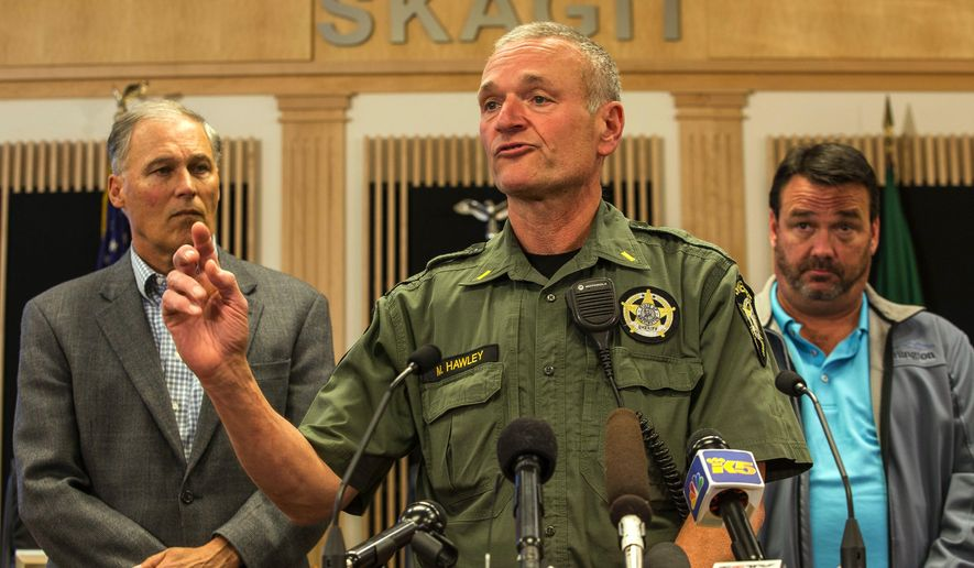 Lt. Mike Hawley with Island County Sheriff's office discusses the capture of Arcan Cetin, 20, who was wanted in connection with Friday's mass shooting at Cascade Mall in Burlington, Wash. on Friday.  Officials, including Washington Gov. Jay Inslee, left, gathered in the Skagit County chambers in Mt. Vernon, Wash. Saturday, Sept. 24, 2016.   (Dean Rutz / The Seattle Times via AP)