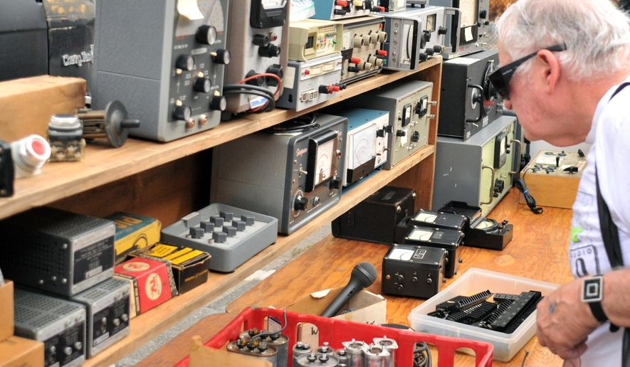 In this Sept. 18, 2016, photo, Joel Goldberg, of Newton, Mass., browses MIT's Radio Society flea market on the campus of the Massachusetts Institute of Technology in Cambridge, Mass. Every third Sunday, MIT's Radio Society hosts a parking-lot flea market that's part yard sale and part curio museum from the world of electronics. Vendors come to hawk radio equipment, but also vintage Macintosh computers, castaway musical instruments, baubles of all kinds and the occasional space capsule. The storied market is part of a circuit of flea markets hosted by radio clubs across New England, but this one is known for attracting the strangest of wares. (AP Photo/Collin Binkley)