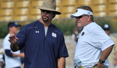 FILE - In an Aug. 29, 2014 file photo, Notre Dame coach Brian Kelly, right, talks with defensive coordinator Brian VanGorder during practice during media day for a NCAA football team in South Bend, Ind. It was announced Sunday, Sept. 25, 2016, that Notre Dame coach Brian Kelly has fired defensive coordinator Brian VanGorder following a 1-3 start. The school tweeted a new release saying VanGorder is being replaced by defensive analyst Greg Hudson.(AP Photo/Joe Raymond, File)