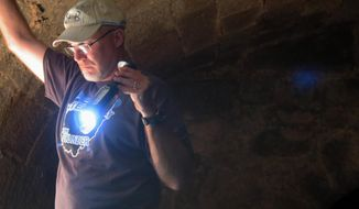 In this Thursday, Sept. 1, 2016 photo, Chuck Foster, a Wheeling Island property owner, shines a flashlight inside his historic wine cellar in Wheeling, W.Va. (Alec Berry/The Intelligencer/Wheeling News-Register via AP)