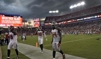 Tampa Bay Buccaneers cornerback Vernon Hargreaves (28), free safety Bradley McDougald (30) and outside linebacker Lavonte David (54) leave the field as storm clouds move over the stadium during the fourth quarter of an NFL football game Sunday, Sept. 25, 2016, in Tampa, Fla. The game is being delayed by weather. (AP Photo/Jason Behnken)