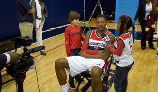 Washington Wizards guard Bradley Beal, interviewed by children at the team's media day on Monday, said he won't always agree with John Wall but they're still teammates. (Associated Press)