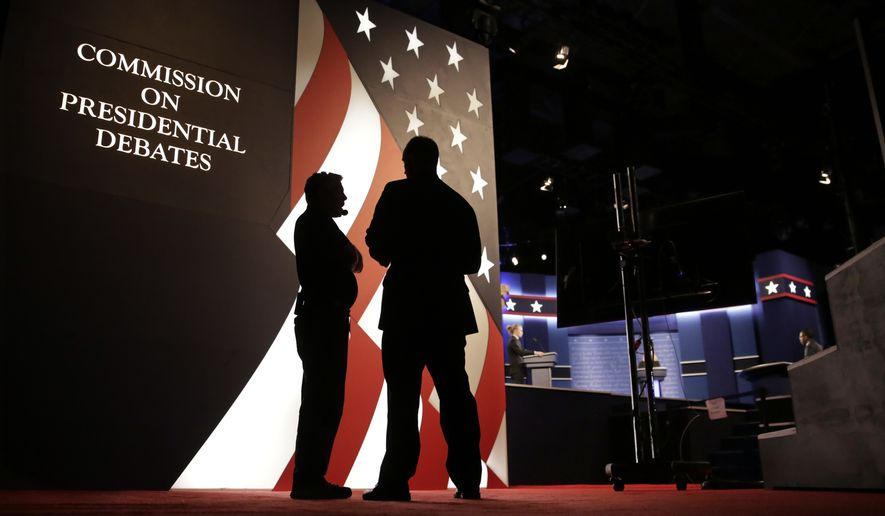 Producers stand next to the stage for the presidential debate between Democratic presidential candidate Hillary Clinton and Republican presidential candidate Donald Trump at Hofstra University in Hempstead, N.Y., Monday, Sept. 26, 2016. (AP Photo/David Goldman)