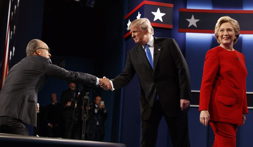 Republican presidential candidate Donald Trump, center, shakes hands with moderator Lester Holt, left, as Democratic presidential candidate Hillary Clinton walks to her lectern during the first presidential debate at Hofstra University, Monday, Sept. 26, 2016, in Hempstead, N.Y. (AP Photo/ Evan Vucci)