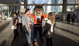 Fans ask for having their picture taken with the new Edmonton Oilers Mascot, a Lynx named Hunter, before a preseason NHL hockey game against the Calgary Flames in Edmonton, Canada, Monday, Sept. 26, 2016. (Jason Franson/The Canadian Press via AP)