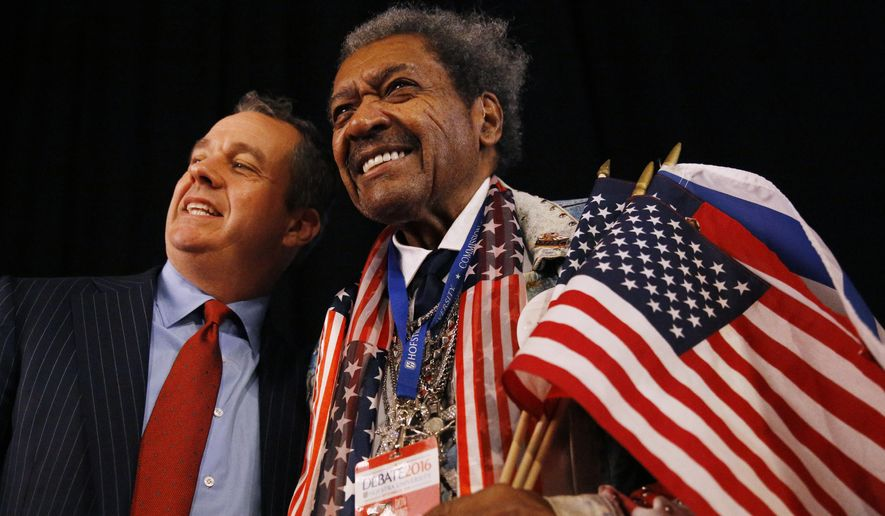Boxing promoter Don King (right) poses with a guest before the presidential debate Monday at Hofstra University in Hempstead, New York. (Associated Press)