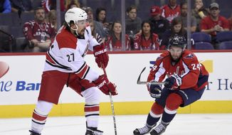 Carolina Hurricanes defenseman Justin Faulk (27) skates with the puck against Washington Capitals forward Riley Barber (24) during the first period of an NHL preseason hockey game, Monday, Sept. 26, 2016, in Washington. (AP Photo/Nick Wass)