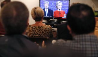A bipartisan group of friends and colleagues of two former Colorado lawmakers from both sides of the aisle, former US Rep. Spencer Swalm, a Republican, and former US Rep. Joe Miklosi, a Democrat, listen to the first presidential debate during a watch party at Swalm's house in Centennial, Colo., Monday, Sept. 26, 2016. (AP Photo/Brennan Linsley)