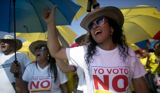 "Demonstrators yell ""No to the plebiscite"" to protest the government's peace agreement with the Revolutionary Armed Forces of Colombia (FARC), to be signed later in the day in Cartagena, Colombia, Monday, Sept. 26, 2016. Colombians will be given the final say on endorsing or rejecting the accord in an Oct. 2 referendum.  (AP Photo/Ariana Cubillos)"