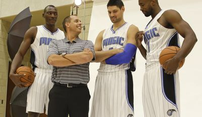 Head coach Frank Vogel, second from left,  and Orlando Magic players, from left, Bismack Biyombo, Nikola Vucevic, and Serge Ibaka (7) joke around before a photo during the team's NBA basketball media day, Monday, Sept. 26, 2016, in Orlando, Fla.  (AP Photo/John Raoux)