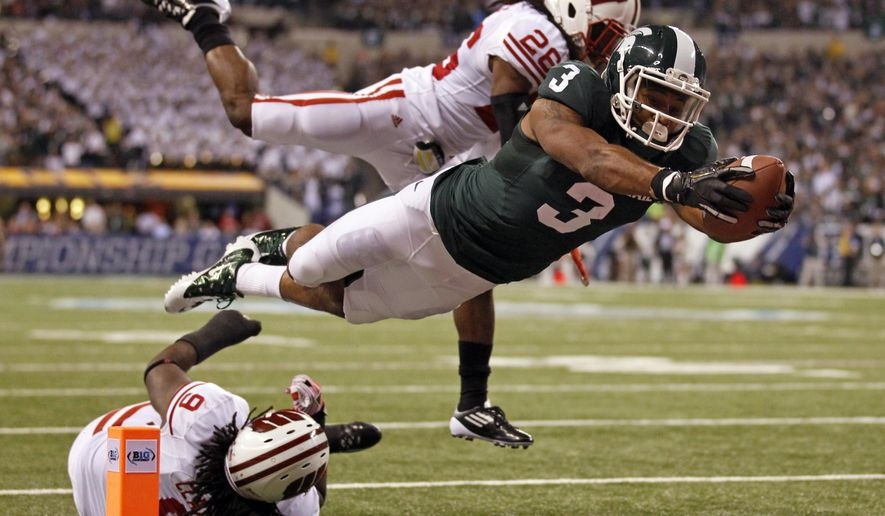 File-This Dec. 3, 2011, file photo shows Michigan State's B.J. Cunningham (3) diving into the end zone for a touchdown in front of Wisconsin's Antonio Fenelus during the Big Ten conference championship NCAA college football game , in Indianapolis.  The eighth-ranked Spartans finally renew their series with 11th-ranked Wisconsin on Saturday _ their first meeting in East Lansing since that Hail Mary. Both teams already have notable wins this season, Michigan State over Notre Dame and Wisconsin over LSU. (AP Photo/Michael Conroy, File)
