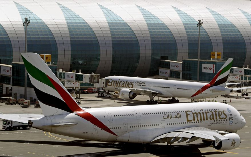 FILE- In this May 8, 2014 file photo, Emirates passenger planes are in use at Dubai airport in United Arab Emirates. Dubai Airports said Monday it plans to add 10 more A380 gates with air bridges at Dubai International Airport's Concourse C. That will leave the airport with a world record 47 gates designed for the aircraft. (AP Photo/Kamran Jebreili, File)