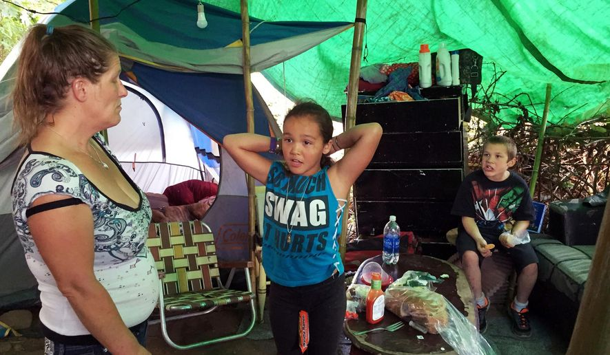FILE - In this Aug. 10, 2016 file photo, Deitra Schmer watches as her granddaughter, Andrea Brown, brushes her hair and grandson Adrian Atkinson, right, look on in Schmer's tent in a homeless encampment along the Springwater Corridor bike and pedestrian trail in Portland, Ore. Five major hospitals in Portland and a low-income, nonprofit health plan are donating a combined $21.5 million to build nearly 400 housing units for the city's homeless population, Friday, Sept. 23, 2016. (AP Photo/Gillian Flaccus,File)