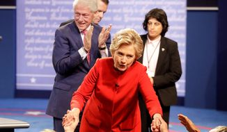 Democratic presidential nominee Hillary Clinton greets supporters as her husband, former President Bill Clinton, applauds. She ignored Mr. Trump's chiding remarks during the debate and instead tried to bait him. (Associated Press)