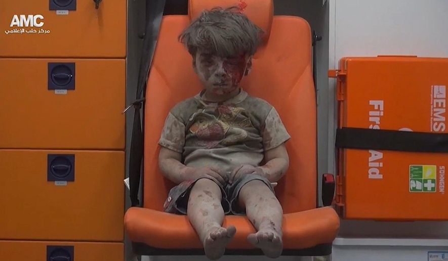 """Five-year-0ld Omran Daqneesh sits in an ambulance after being pulled out of a building hit by an airstrike in Aleppo, Syria. White Helmets chief Raed al-Saleh said the city's 275,000 civilians are """"sitting in their homes, waiting to die"""" amid airstrikes. (Associated Press)"""