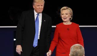 Republican presidential nominee Donald Trump and Democratic presidential nominee Hillary Clinton walk across the stage after the presidential debate at Hofstra University in Hempstead, N.Y., Monday, Sept. 26, 2016. (AP Photo/David Goldman)