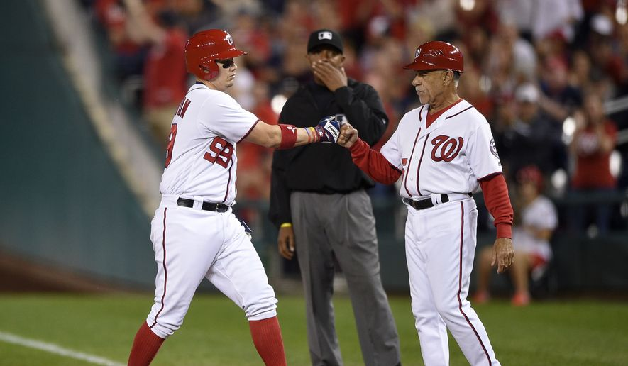 Washington Nationals' Jose Lobaton, left, fist bumps first base coach Davey Lopes, right, as he stands on first with a single during the sixth inning of a baseball game against the Arizona Diamondbacks, Tuesday, Sept. 27, 2016, in Washington. (AP Photo/Nick Wass) **FILE**