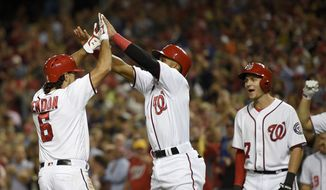 Washington Nationals' Anthony Rendon (6) celebrates his three run home run with Wilmer Difo, center, and Trea Turner, right, during the sixth inning of a baseball game against the Arizona Diamondbacks, Tuesday, Sept. 27, 2016, in Washington. (AP Photo/Nick Wass)