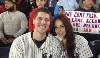 Andrew Fox, left, and Heather Terwilliger sit in the stands at Yankee Stadium on Tuesday night, Sept. 27, 2016, in New York. When Fox pulled the ring from his pocket and dropped to one knee before Terwilliger to propose during the fifth inning of the Yankees' game, the ring dropped to the ground. A frantic search ensued. After about five minutes, Terwilliger looked down and saw something shiny in the cuff of her pants leg. (Scott Orgera via AP)
