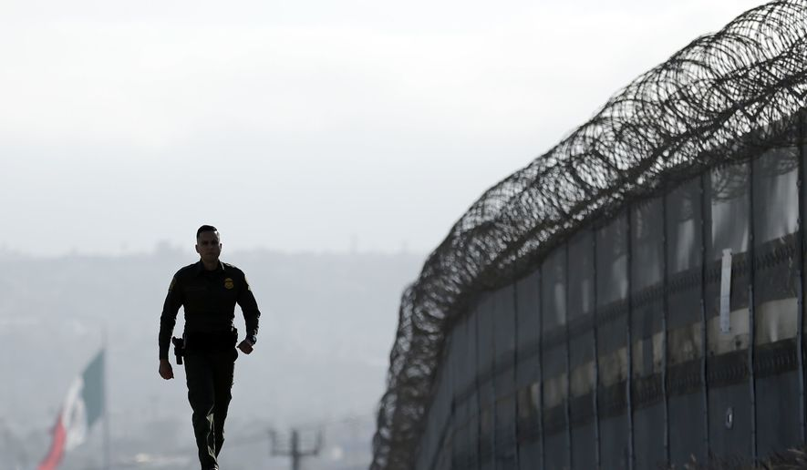Border Patrol agent Eduardo Olmos walks near the secondary fence separating Tijuana, Mexico, and San Diego. (Associated Press) ** FILE **
