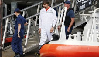 Nathan Carman, center, disembarks from a small boat at the US Coast Guard station in Boston, Tuesday, Sept. 27, 2016. Carman spent a week at sea in a life raft before being rescued by a passing freighter. (AP Photo/Michael Dwyer)