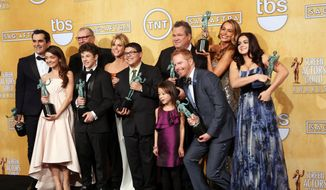 """The cast of """"Modern Family"""" poses with their awards for outstanding performance by an ensemble in a comedy series fat the 20th annual Screen Actors Guild Awards at the Shrine Auditorium in Los Angeles, Jan. 18, 2014. (Photo by Matt Sayles/Invision/AP) ** FILE **"""